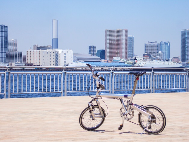 川沿いにたたずむ折りたたみ自転車