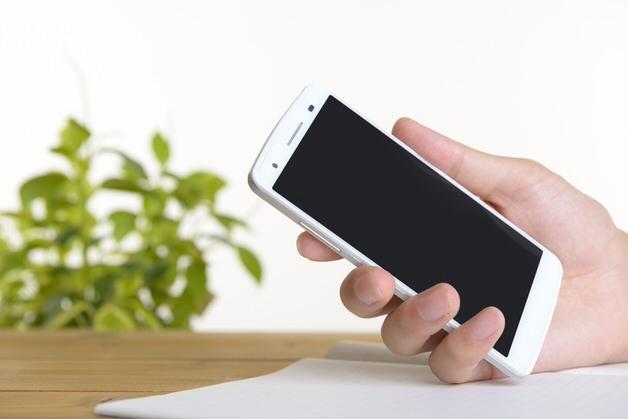 白いスマートフォンを持つ手