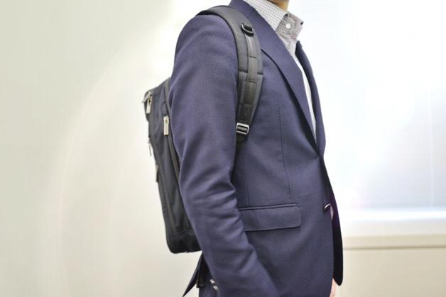 リュックサックを背負ったビジネススーツの男性